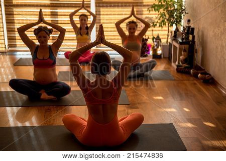 Relax lesson. Impregnate ladies are sitting on yoga mats and looking at teacher with smile. They rising hands up