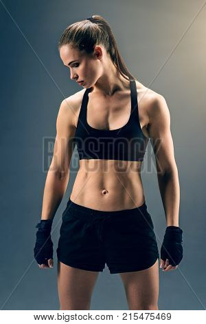 Ready to fight. Focused female athlete wearing a dark sport clothing standing on feet shoulder width apart and making up her mind to fight.