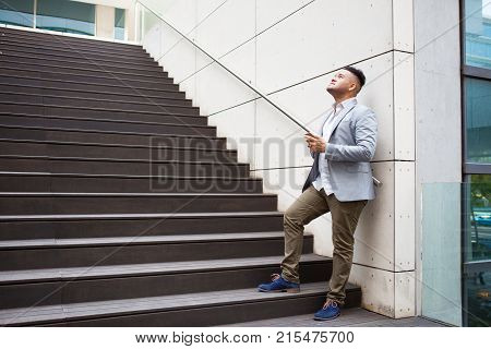 Pensive mixed race businessman thinking of text for message. Serious young blogger finding inspiration for post while looking up at sky. Thoughtful male manager looking for answers. Thoughts concept