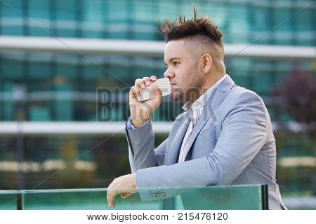 Puzzled businessman thinking of difficulties in work and looking into distance. Pensive handsome man with smartphne in hand leaning on railing outdoors reflecting about business. Contemplation concept