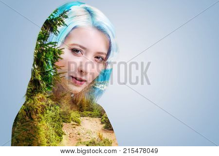 Dreamy mood. Serene young woman standing against the background and posing with wistful smile while looking into the camera.