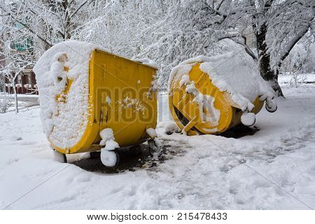 Yellow trash can covered with snow. Municipal economy