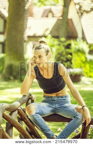 Pretty girl or beautiful fit woman in sexy black undershirt and blue jeans sits on wooden palisade on sunny summer day outdoors on natural background