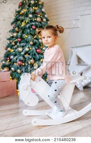 Girl 3 years old riding a horse. Concept New Year Merry Christmas holiday vacation winter childhood.