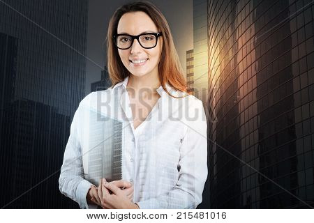 Loving my job. Waist up shot of a friendly looking young woman in a formalwear and glasses looking into the camera with a cheerful smile on her face while standing with a notepad in her hands.