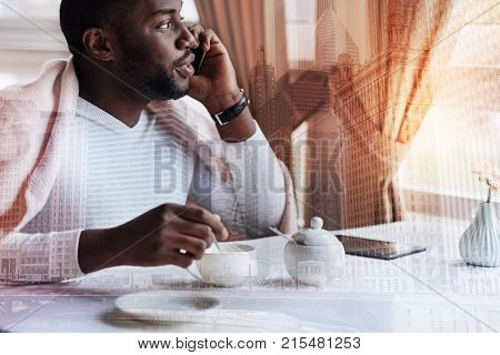 Important conversation. Young clever concentrated man sitting in a comfortable cafe and talking on the phone with his colleague while looking into the window