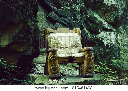 One big wooden cut beautiful arm chair as forest queen fairytale throne standing in wood with no people outdoor on grey stone natural background horizontal picture