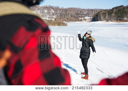 Couple Having A Snowball Fight On A Sunny Day