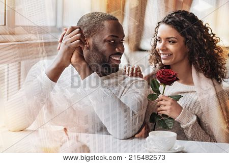 Having a date. Cheerful young couple looking at each other while expressing happiness and delight