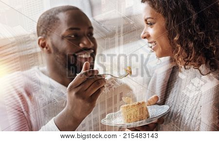 Pleasant date. Optimistic young couple looking at each other with love while eating tasty dessert and expressing cheer