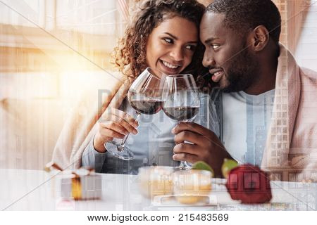 True love. Close up of young optimistic couple having wonderful date while looking at each other and holding glasses with wine