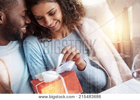 Perfect present. Close up of delighted young couple showing happiness while hugging each other and being pleased