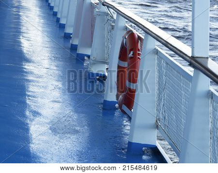 The deck of a ship with hanging on the bulwark red lifeline