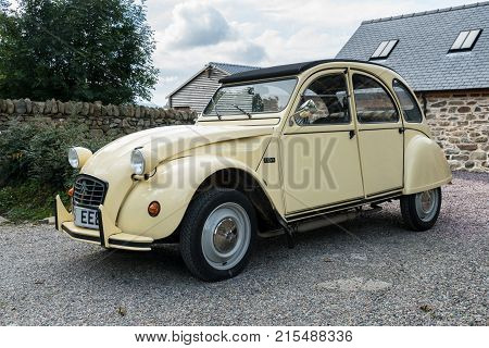 OSWESTRY, UK - SEPTEMBER 24, 2016: Restored cream colored Citroen 2CV6 french car in driveway of old house