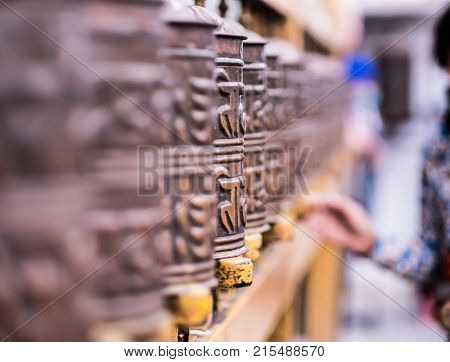 Prayer wheels and woman who pray at Boudhanath Stupa in Kathmandu, Nepal