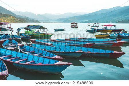 Colourful boats on the water of Phewa lake, Nepal