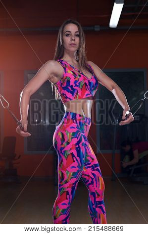 Beautiful slender young sportswoman in colored wear posing holding the handles of the simulator in the gym
