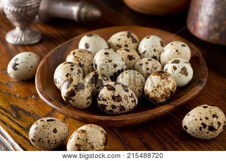 Quail eggs in a wooden bowl on a rustic table top setting.