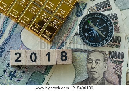 Wooden block with number 2018 gold bullion and compass on pile of japanese yen banknotes as year 2018 financial safe haven or tax concept.