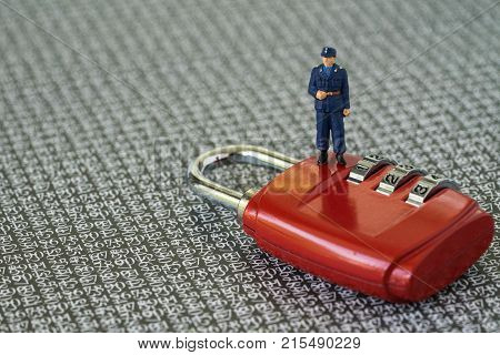 Computer security or hacker protection concept with miniature figure security guard standing on red combination lock pad with the background of computer numbers secret code.