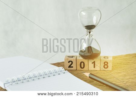 Number 2018 wooden cube block with sandglass/hourglass and white paper note book with pencil on wooden table as New year 2018 goals target aim with timeline or checklist concept.