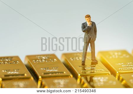 Miniature figure businessman standing on shiny gold bullions ingot bar with artificial light as successful rich man of financial investment and wealth concept.