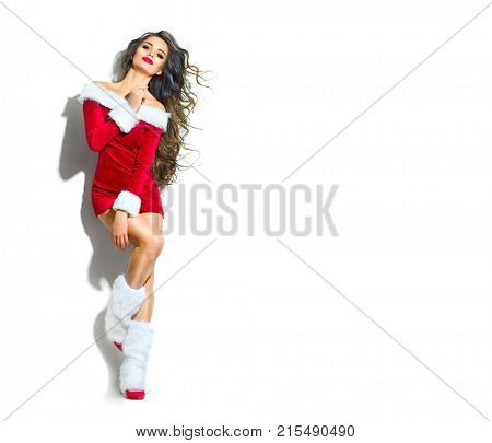 Beauty Christmas fashion model girl, wearing red santa dress. Sexy brunette young woman with long curly hair. Stylish female fashionable party clothes and accessories makeup and hairstyle. Full length