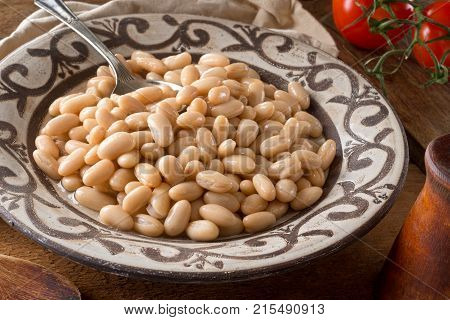 A bowl of white kidney beans on a rustic wooden table top.