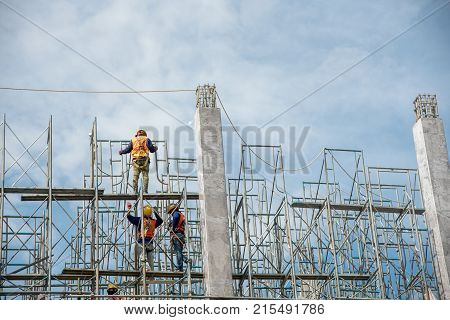 Group Of Worker In Safety Uniform Install Reinforced Steel Column In Construction Site During Sunset