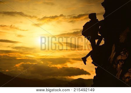 Silhouette of young woman lead climbing high Hanging on rock above clouds and mountains at sunset.