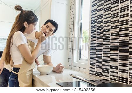 Sweet couple home kitchen cooking lover concept.Young asian woman holding salad to man eating each for cooking dinner healthy food menu in kitchen romantic.