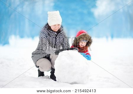 Little boy with his mother babysitter grandmother building snowman in snowy park. Active outdoors leisure with children in winter. Kid during stroll in a snowy winter park