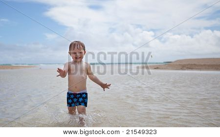 Happy toddler running in the water on a tropical beach