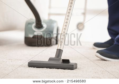 Young man cleaning carpet with vacuum cleaner in living room