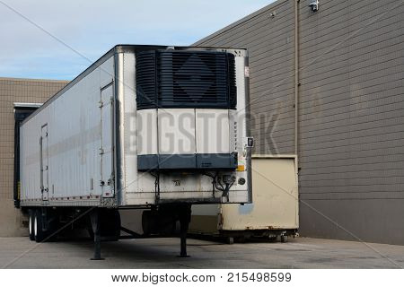 Shipping truck trailer parked at receiving door of business or grocery store