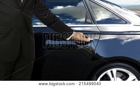 Driver hand getting ready to open black car door