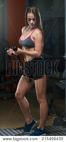 Beautiful slim young woman in sport suit and sneakers doing exercises in the gym