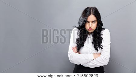 Unhappy young woman on a solid background