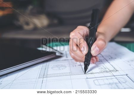 Closeup image of architects drawing shop drawing paper with mass model on table