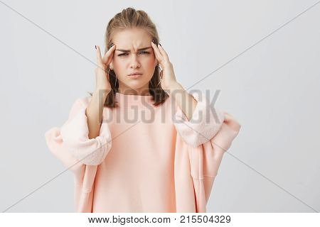 Cute pretty caucasian young woman dressed in pink sweatshirt frowning her face looking tired holding her hands on temples because of tiredness or headache. Young woman having sad expression and headache. People, problems, tiredness concept