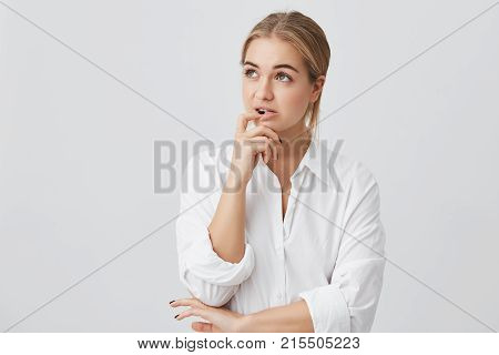 Horizontal portrait of confused woman with fair dyed straight hair, holding her finger on teeth making difficult choice not knowing what to choose.