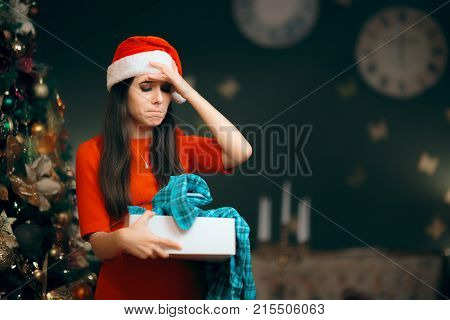 Upset Girl Opening a Bad Christmas Gift Finding Pajamas Inside