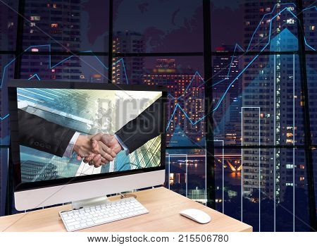 the computer on the wood table with Hand shake between businessman at the screen on the trading graph over the blurred photo of cityscape background Elements of this image furnished,