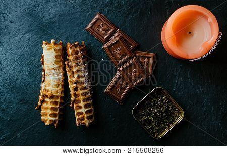 Chocolate, tea, candle and waffer tubes on black kitchen desk