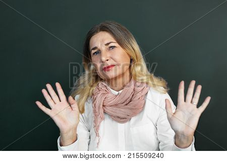 Horizontal studio shot of annoyed displeased middle aged female reaching out open palms showing stop gesture as sign of denial refusal prohibition restriction saying: Stay away from me