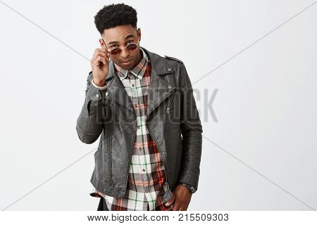 Portrait of stylish attractive young dark-skinned african male model with curly hair in black leather outwear taking off sunglasses with hand, looking in camera with cool and calm expression