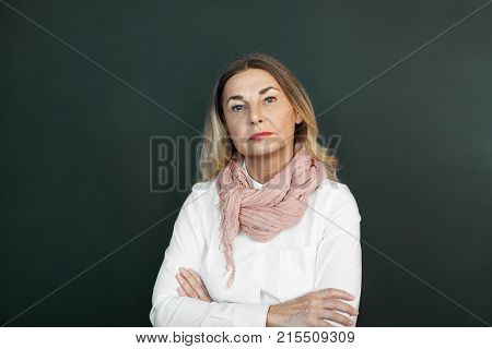 Blonde mature woman with skeptical strict expression on her wrinkled face posing in studio keeping arms folded expressing suspicion or disapproval. Negative human emotions feelings reaction