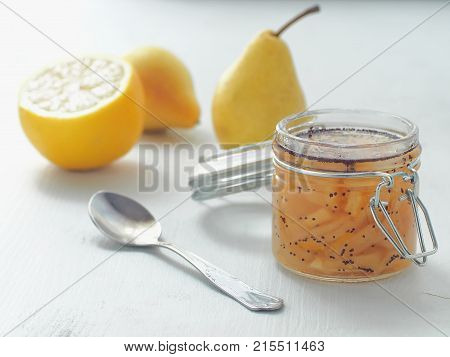 Pear jam in a jar upon rustic table. Selective focus on the jar.