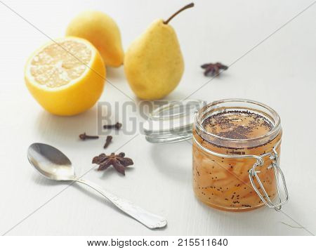 Pear jam in a jar with spices upon white wooden table. Selective focus on the jar.