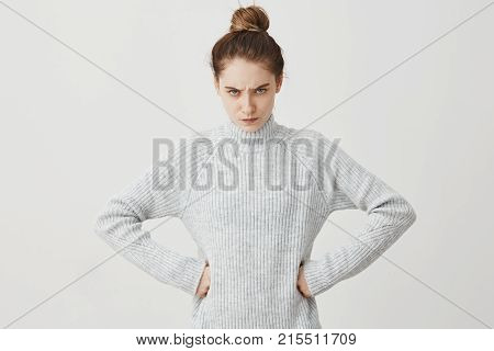 Confident woman looking at camera with angry gaze holding arms at hips. Upset housewife being offended on her husband looking formidable. Relationships, people concept